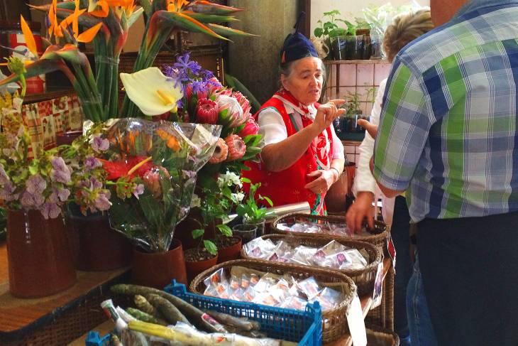 Gehuld in traditionele kleren, verkopen bloemenmeisjes hun waar op de markten in Funchal.