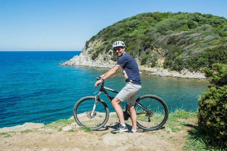 Helder blauw water en rotsachtige kustlijn bij Baratti in Toscane